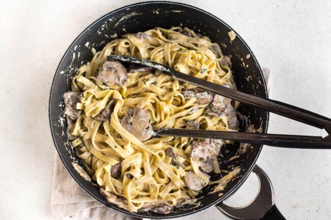 Creamy garlic mushroom tagliatelle in a frying pan.