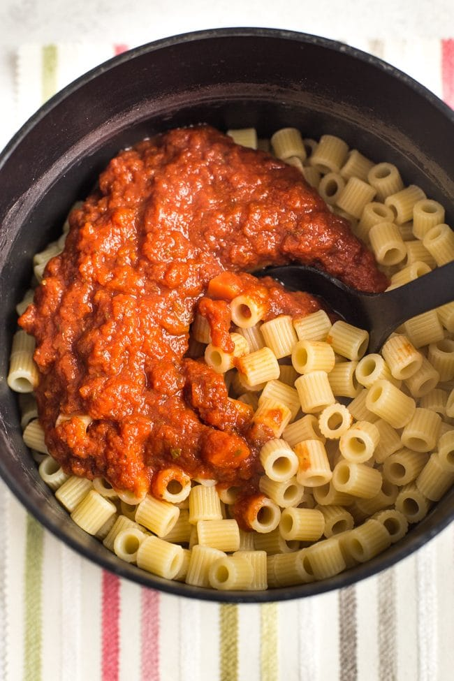Pasta in a saucepan with tomato sauce on top
