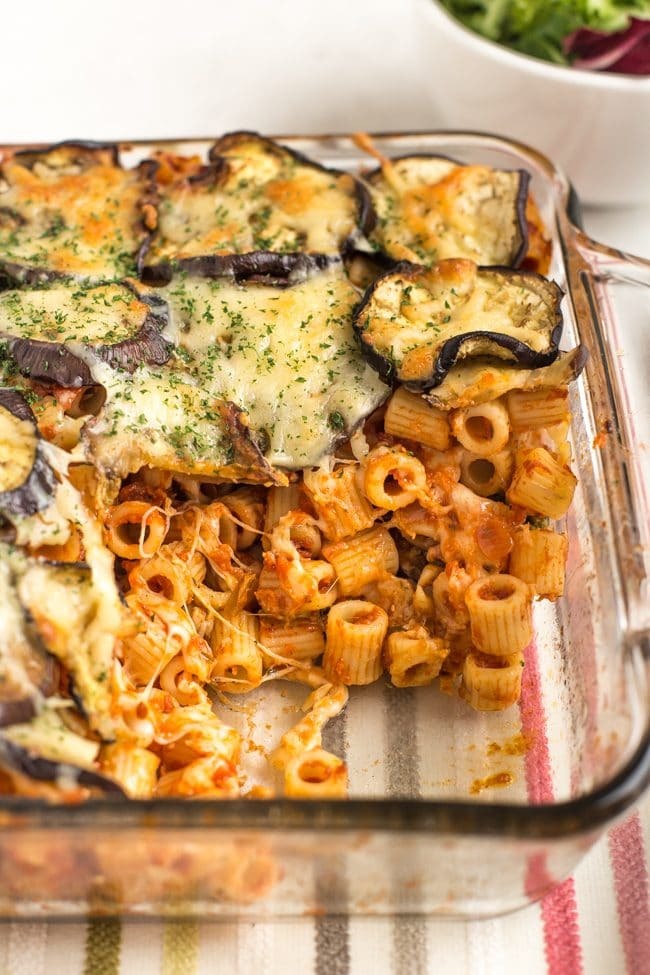 Eggplant parmesan pasta bake in a baking dish with a portion removed