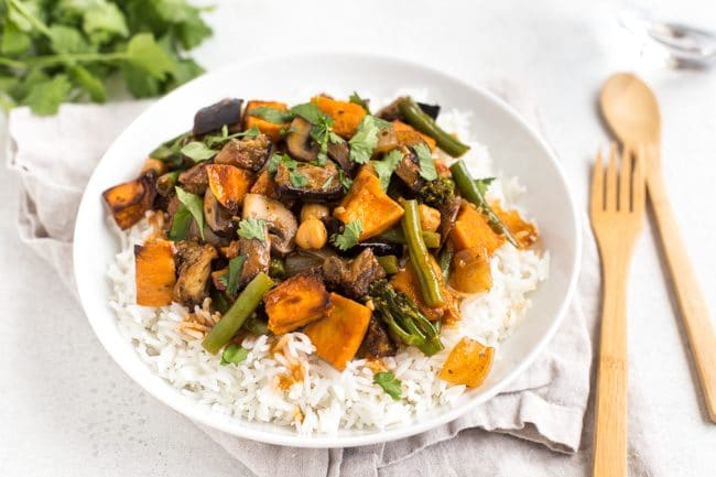 Landscape photo of aubergine and sweet potato Thai red curry in a bowl over rice