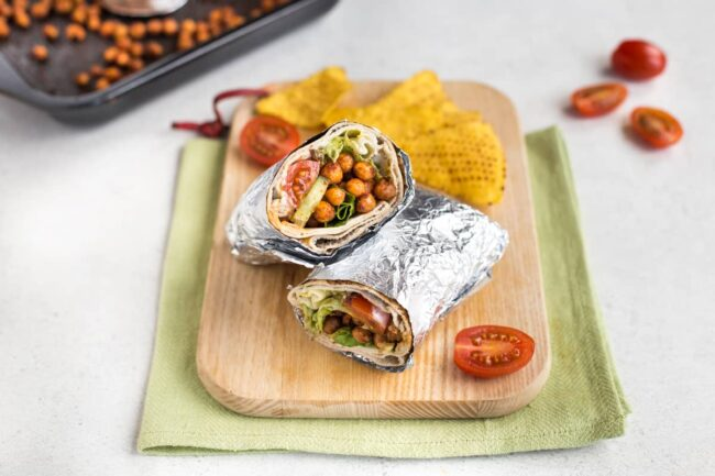 A spicy chickpea salad wrap rolled up in foil and cut in half on a chopping board.