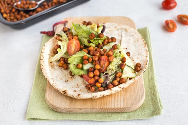 A wrap on a wooden chopping board, topped with salad and spicy roasted chickpeas.