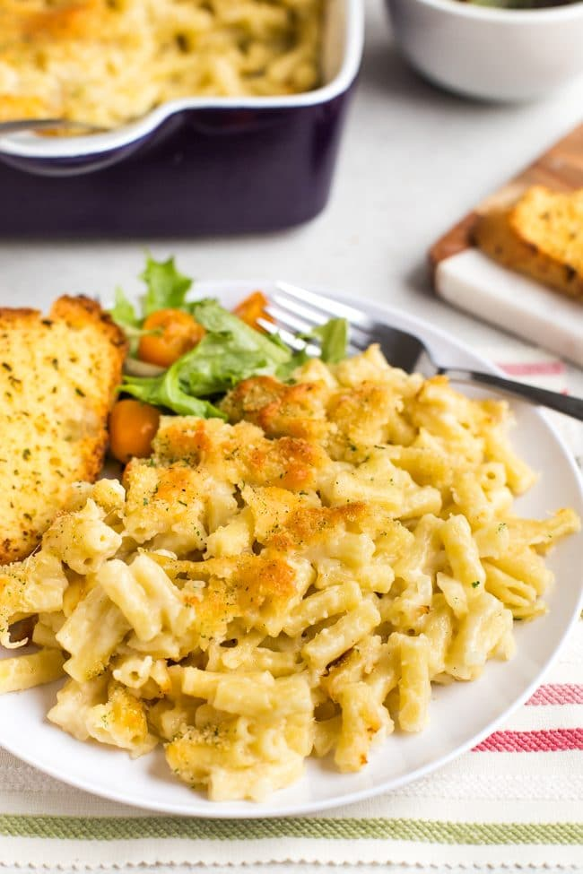 Portion of macaroni cheese on a plate with garlic bread and salad