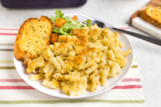 Portion of macaroni cheese on a plate with salad and garlic bread