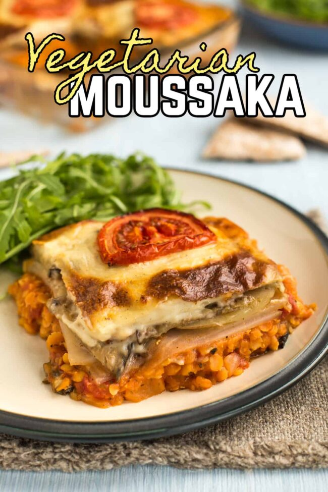 Portion of vegetarian moussaka on a plate, topped with sliced tomato.