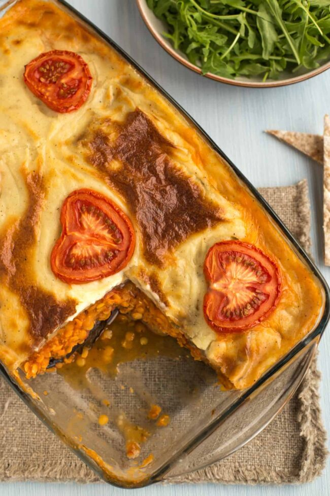 A baked vegetarian moussaka topped with sliced tomatoes, with a portion removed.