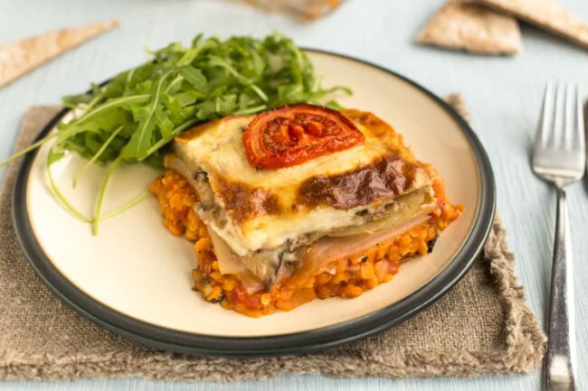A portion of vegetarian moussaka on a plate served with rocket.