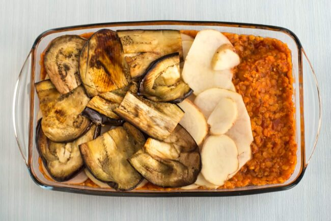 A vegetarian moussaka being layered up in a baking dish with lentils, potatoes and grilled aubergine (eggplant).