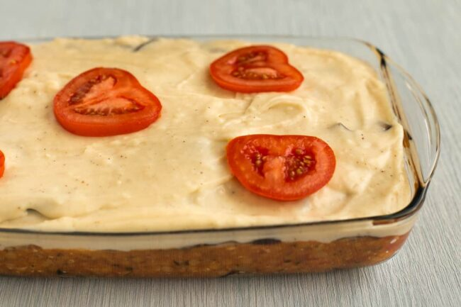 An uncooked vegetarian moussaka in a baking dish topped with sliced tomatoes.