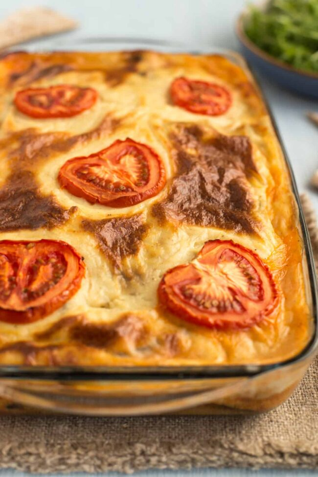 A baked vegetarian moussaka in a baking dish, topped with sliced tomatoes.