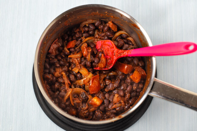 Black beans, onions and tomatoes cooking in a saucepan.