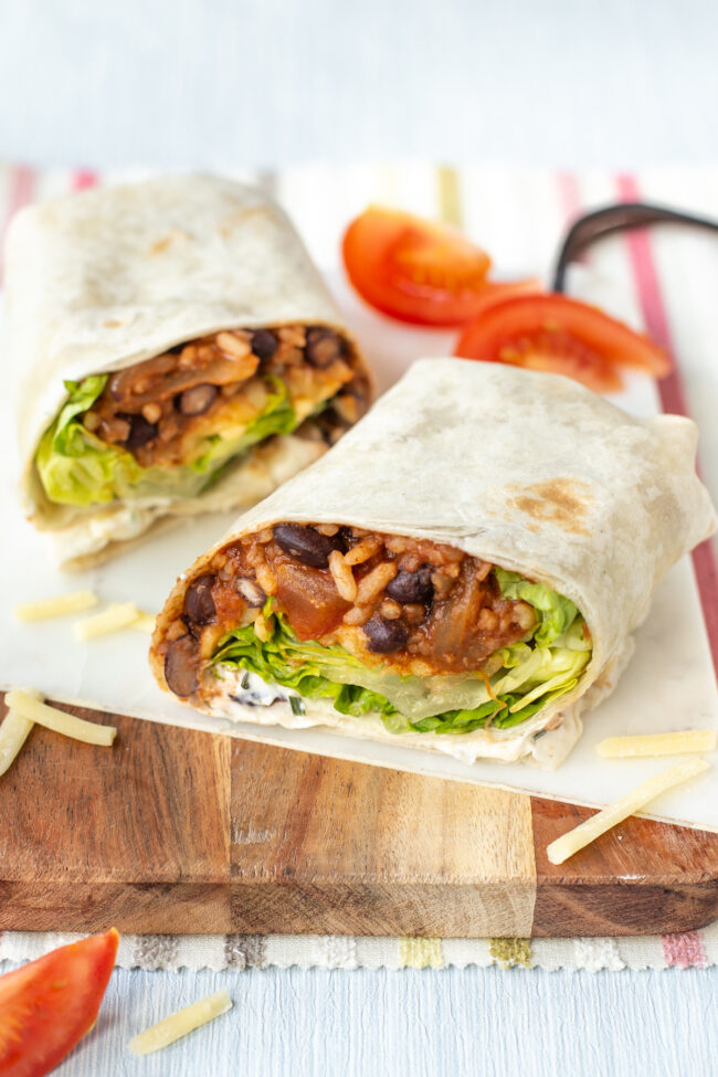 A vegetarian black bean burrito cut in half on a board.