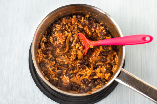 Vegan burrito filling, with rice, black beans and onions, cooking in a pan.