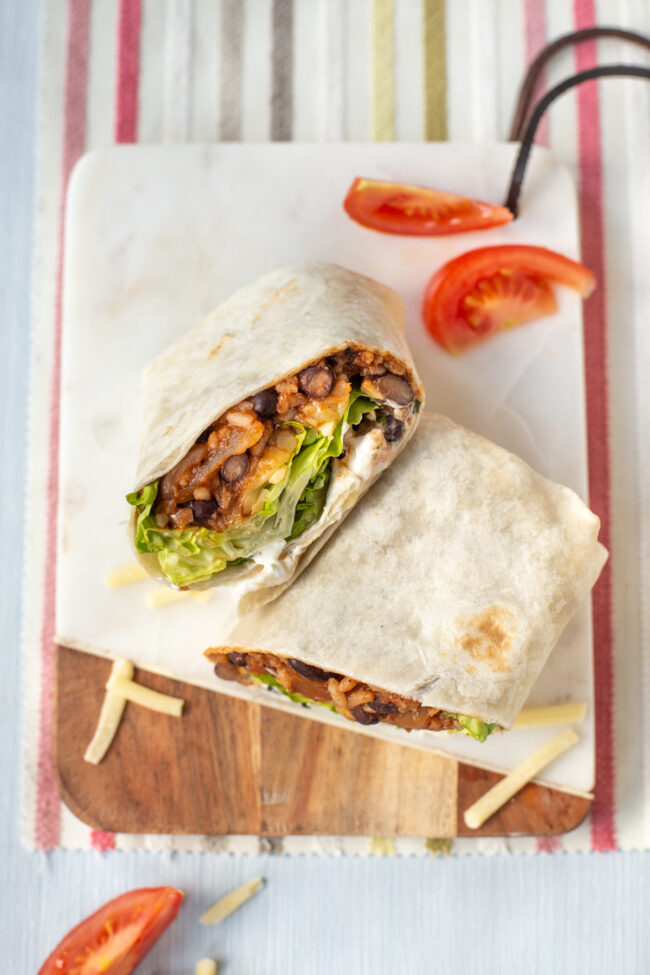 Vegetarian bean burritos stuffed with rice, beans, and lettuce.