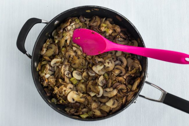 Garlicky mushrooms and leek cooking in a frying pan.