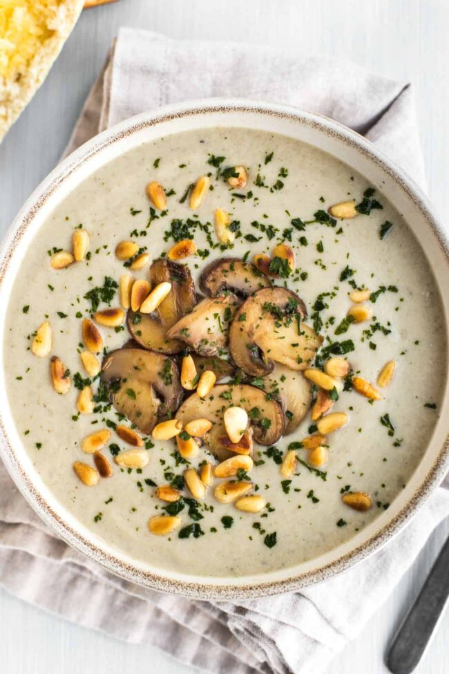 Portion of vegan cream of mushroom soup topped with fried mushrooms and pine nuts.