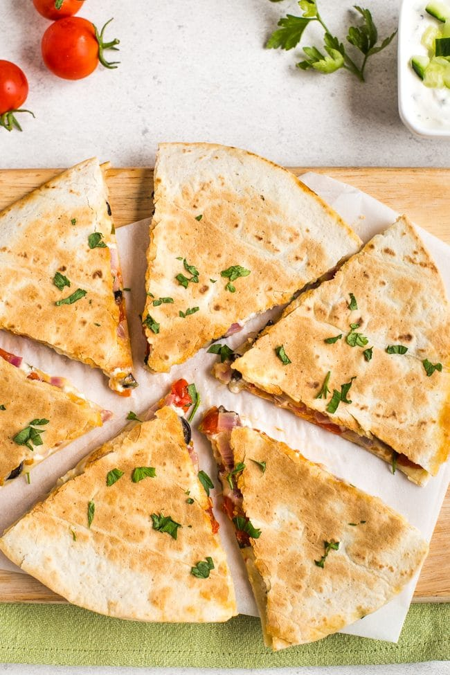 Greek quesadilla on a wooden board, cut into slices, shot from above