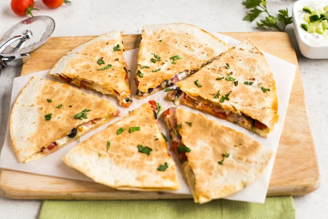 Greek quesadillas on a wooden board, cut into slices