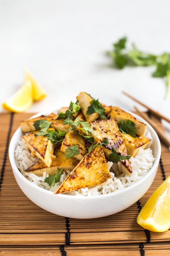 Lemon tofu with rice in a bowl, topped with cilantro