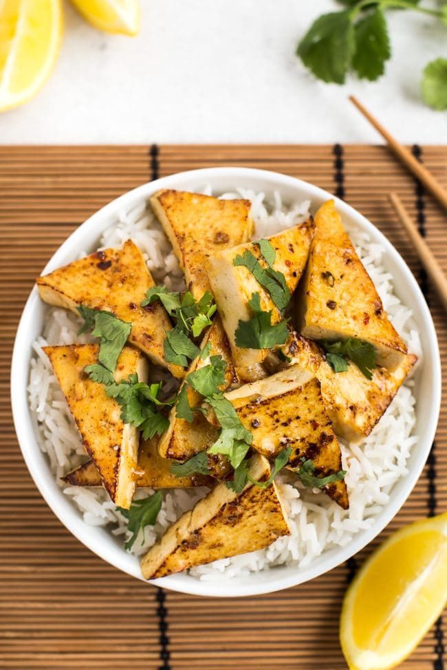 Lemon tofu with rice in a bowl, topped with cilantro, shot from above
