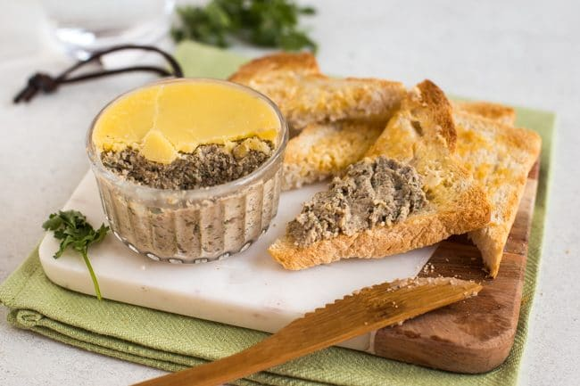 Potted mushroom pate being spread on toast triangles