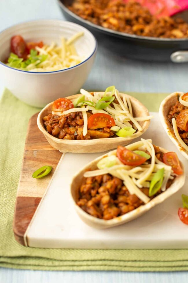 Vegetarian lentil tacos topped with cheese and spring onions.