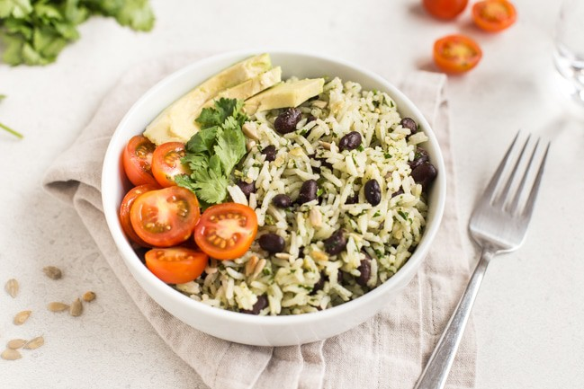 Mexican rice with cilantro pesto and black beans in a white bowl topped with avocado and cherry tomatoes.