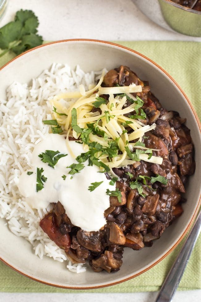 Mushroom and black bean chilli in a bowl with rice, cheese and sour cream