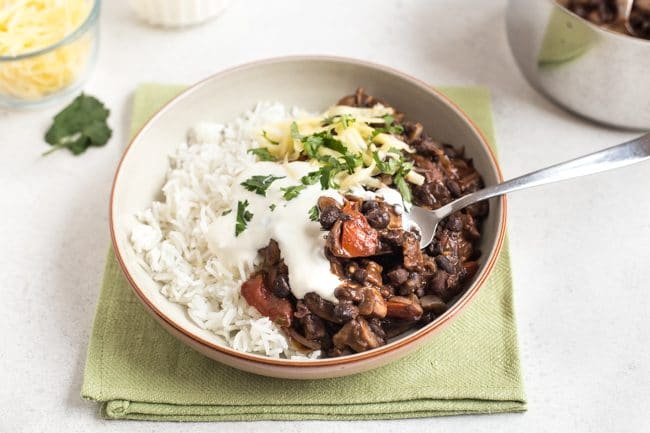 Mushroom and black bean chilli in a bowl with rice and sour cream, with a scoop being taken with a fork
