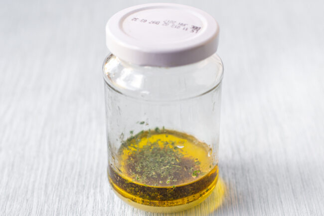 A small glass jar with salad dressing ingredients inside.