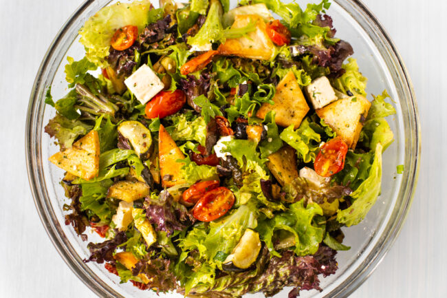 Roasted vegetable fattoush mixed together in a large bowl.