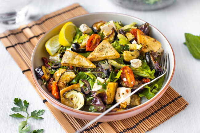 A bowlful of roasted vegetable fattoush with pitta chips and roasted tomatoes.