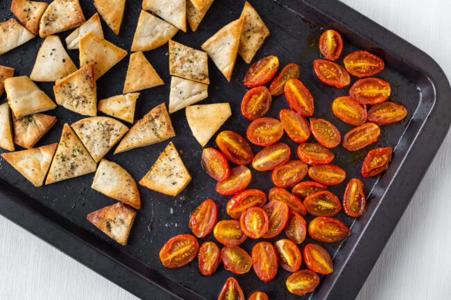 Roasted tomatoes and crispy pitta chips on a baking tray.