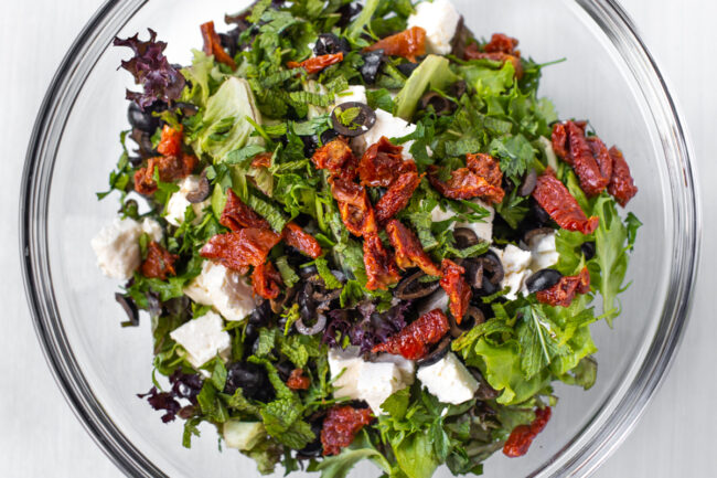 Lettuce, sun-dried tomatoes, feta cheese and olives in a large glass mixing bowl.