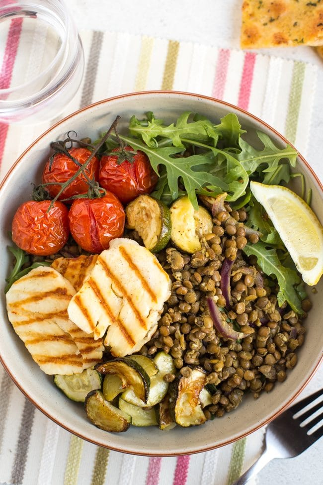 Warm lentil and halloumi salad in a bowl with roasted cherry tomatoes and rocket