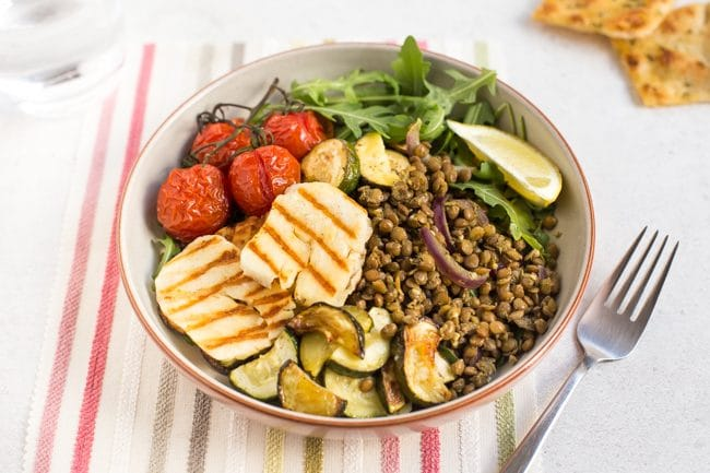 Warm lentil and halloumi salad in a bowl with roasted tomatoes