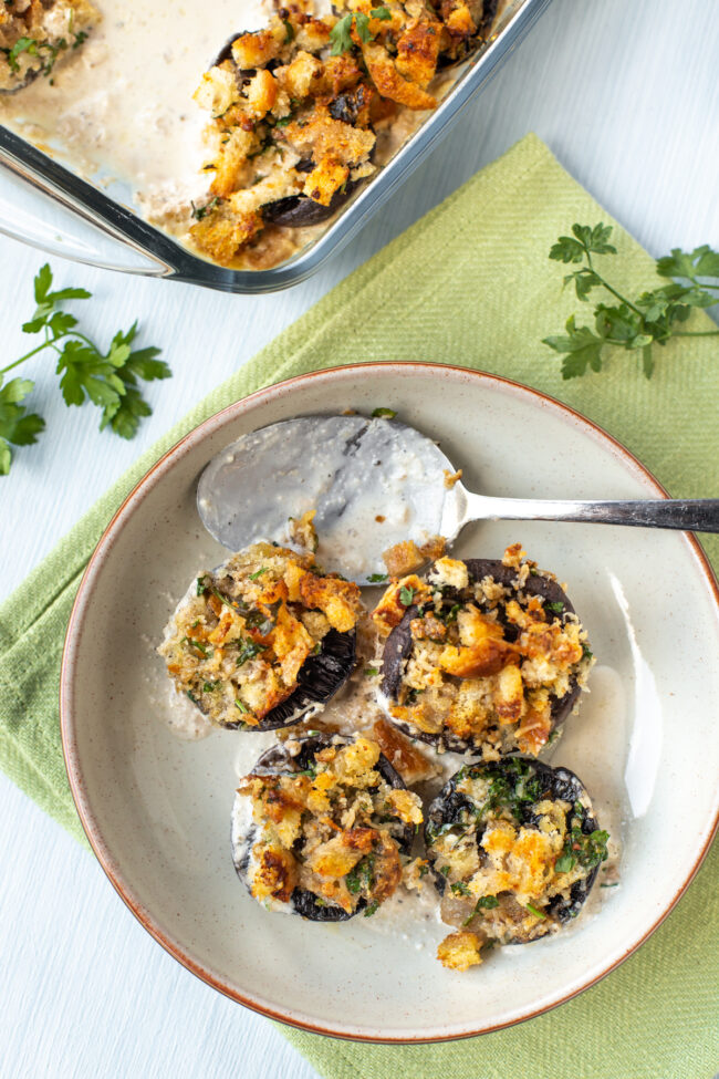Stuffed mushrooms in a bowl with cream sauce.
