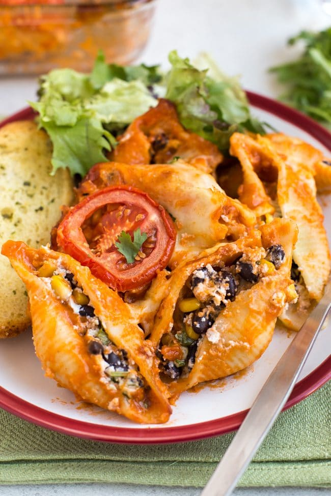 Portion of enchilada stuffed pasta shells on a plate with salad