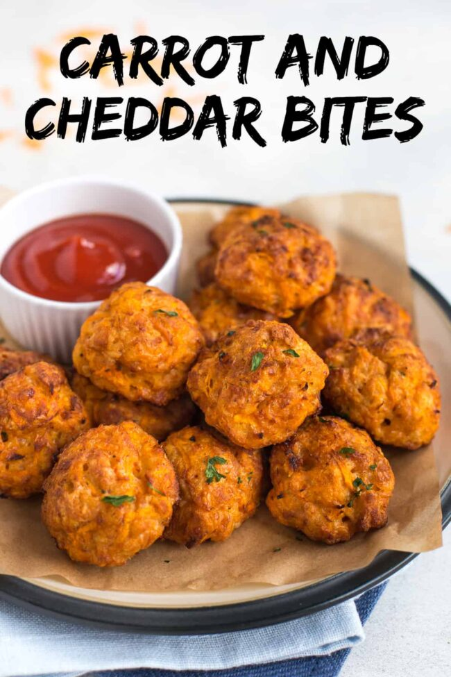 Pile of cheesy carrot and cheddar bites on a plate with a pot of ketchup.
