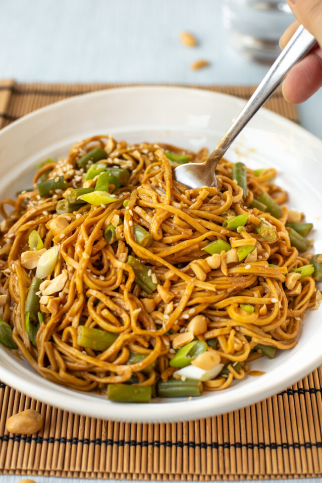 Peanut and sesame noodles being twirled by a fork.