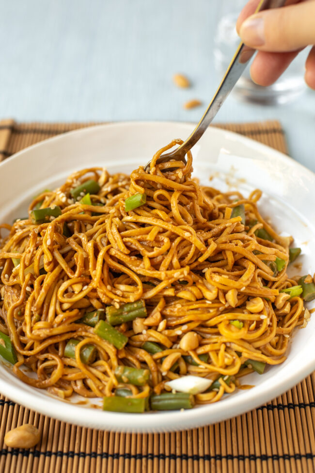 A bowl of peanut and sesame noodles being twirled with a fork.