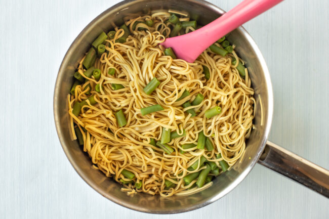 Noodles and green beans in a saucepan.