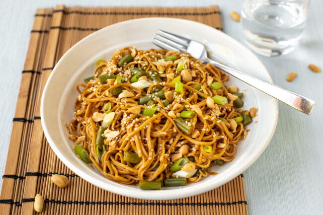 A bowlful of creamy peanut butter noodles topped with green veg and nuts.