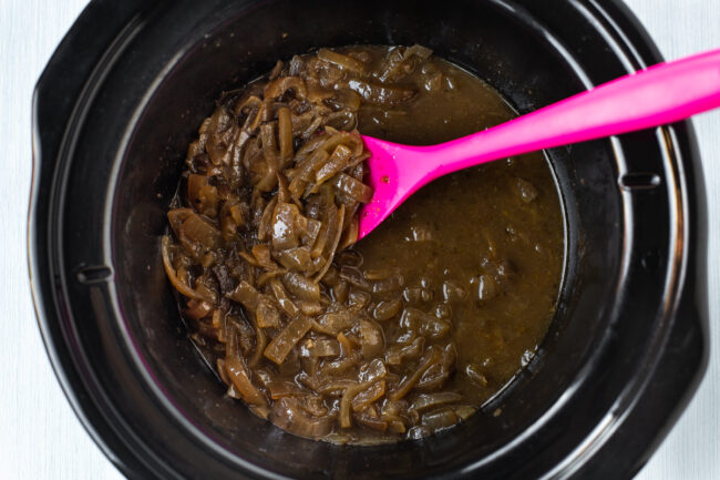 Rich slow cooked French onion soup in a pot.