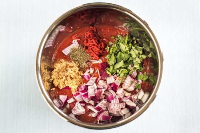Raw ingredients for slow cooker tomato sauce in the pot.