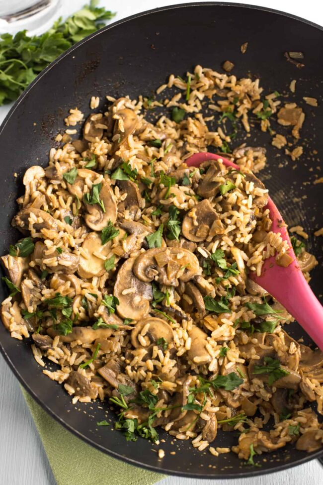 Creamy mushroom stroganoff mixed with rice in a frying pan