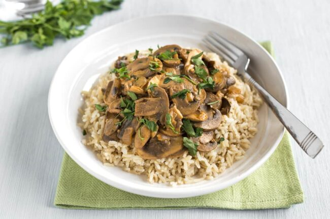 Portion of creamy mushroom stroganoff served on a bed of rice