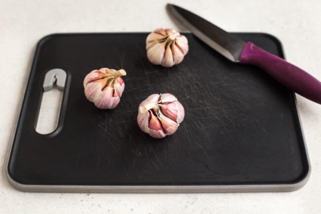 3 heads of garlic on a chopping board.