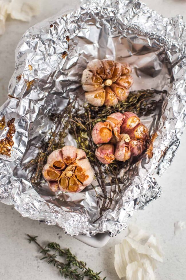 Roasted garlic on a bed of thyme in a foil lined dish.