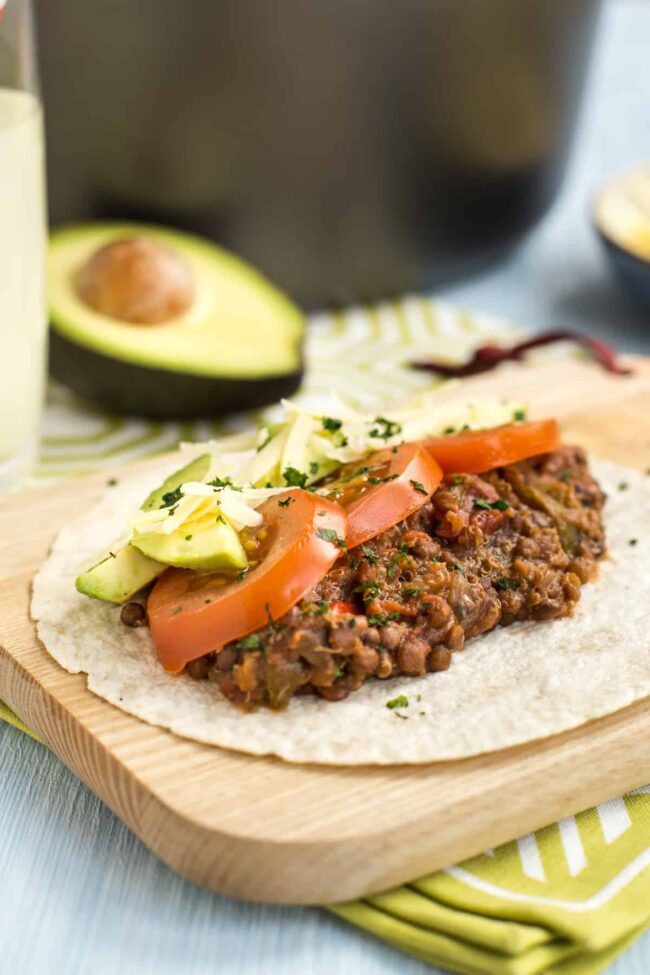 A lentil and quinoa taco topped with sliced tomatoes and avocado.